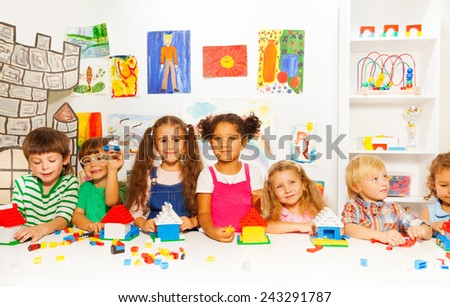 Group of little kids friends play with blocks - stock photo