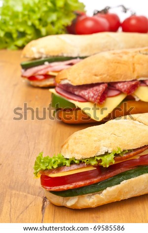 group of long baguette sandwiches with lettuce, vegetables, salami, ham and cheese on a wooden table - stock photo