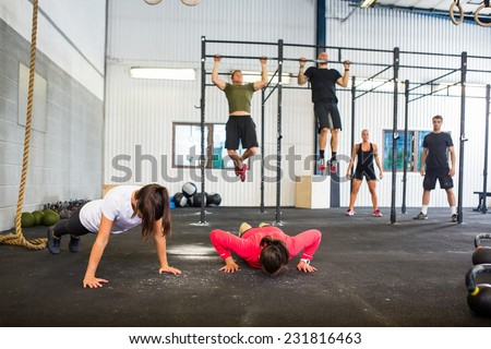 Group of male and female athletes exercising in gym - stock photo