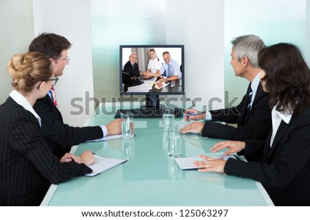 Group of male and female businesspeople seated at a table watching an online presentation on a computer screen - stock photo
