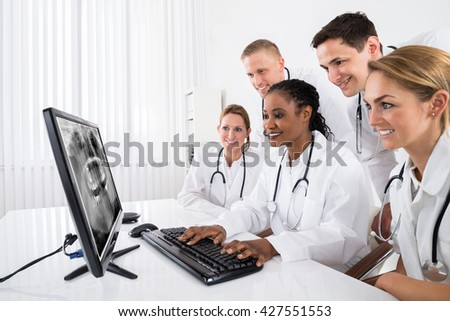 Group Of Male And Female Doctors Looking At X-ray On Computer In Hospital - stock photo