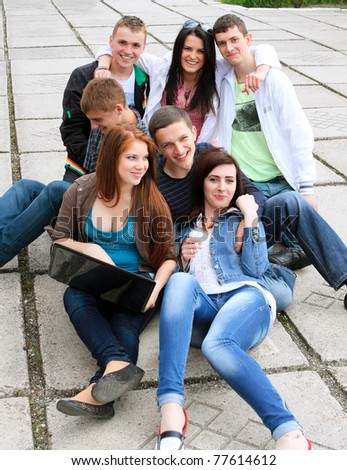 Group of male and female students sitting with a laptop on street - stock photo
