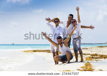 Group of male friends on holidays at the beach - stock photo