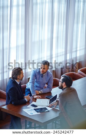 Group of male managers gathered by table in office - stock photo