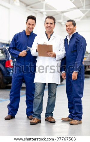Group of male mechanics smiling at a car repair shop - stock photo