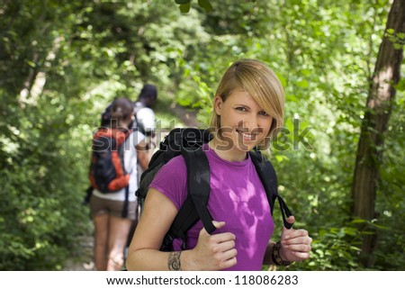 group of man and women during hiking excursion in woods, with woman looking at camera and smiling. Waist up - stock photo
