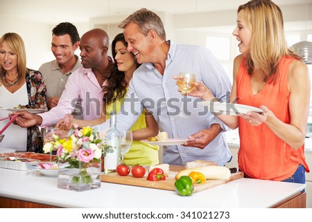 Group Of Mature Friends Enjoying Buffet At Dinner Party - stock photo