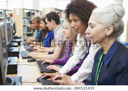 Group Of Mature Students Working At Computers With Tutor - stock photo