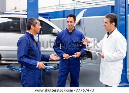 Group of mechanics talking about a car problem - stock photo
