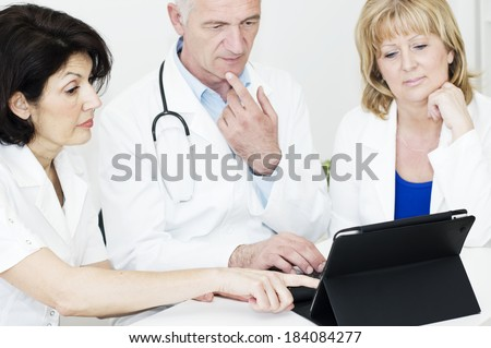 Group of medical personnel sitting at the desk and working at digital tablet together . - stock photo