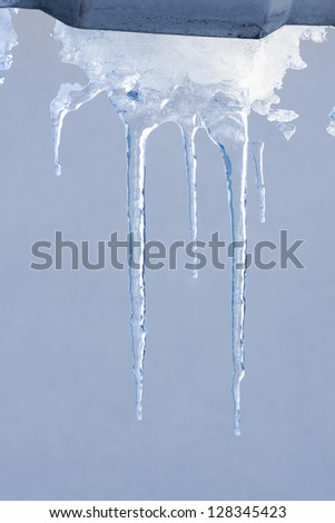 Group of melting icicles against a winter sky - stock photo