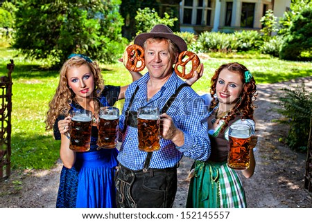 Group of men and women in traditional german Tracht with beer and pretzel - stock photo