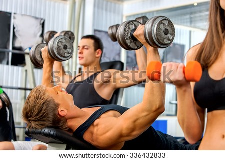 Group of men and women working on simulator his body at gym.  - stock photo