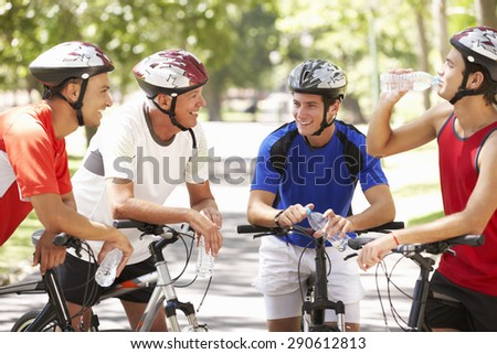 Group Of Men Resting During Cycle Ride Through Park - stock photo