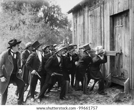 Group of men with guns and top hats breaking into a barn - stock photo