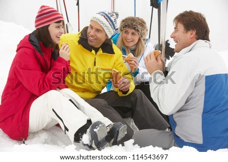 Group Of Middle Aged Friends Eating Sandwich On Ski Holiday In Mountains - stock photo