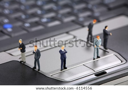 Group of miniature businessmen standing on a laptop. Modern business concept. - stock photo