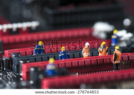 Group of Miniature Engineers Fixing Computer Circuit Board. Macro photo - stock photo