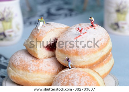 Group of miniature people pulls skiing with donuts. The concept of sports and cooking. - stock photo