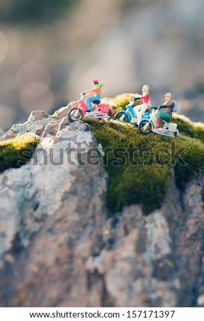 Group of miniature people traveling through the countryside on vintage motorcycles - stock photo