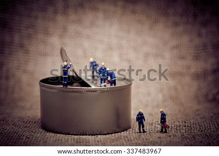 Group of miniature workers opening a can. Color tone tuned macro photo. Macro photo - stock photo