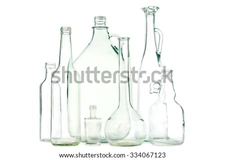 Group of mixed clear colorless glass bottles or glass waste on white - stock photo