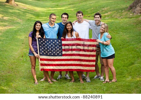 Group of mixed race college students holding an American flag - stock photo