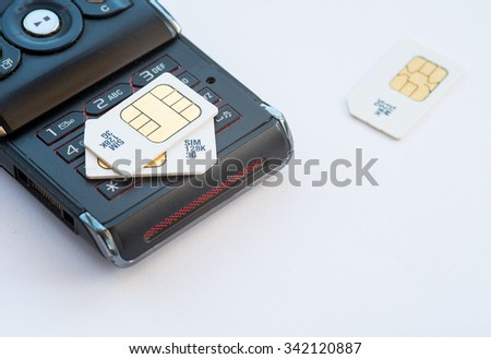 Group of mobile subscriber Identity Module, 3g memory sim cards  on a used black mobile - stock photo