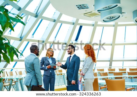 Group of modern employees interacting in office - stock photo