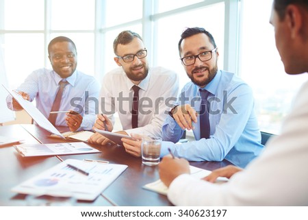 Group of modern employees looking at their colleague during discussion - stock photo