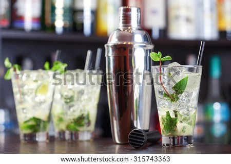 Group of Mojito cocktails on a bar counter with cocktail shaker next to them - stock photo