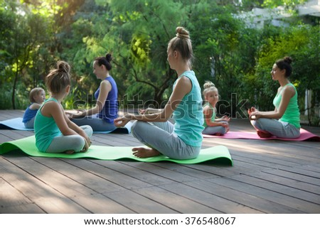 Group of mothers and daughters doing exercise practicing yoga outdoors. Healthy lifestyle - stock photo