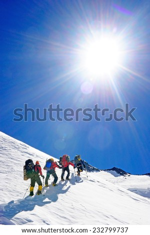 Group of mountain backpackers walking on snow - stock photo