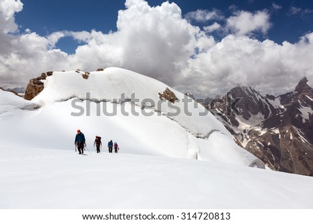 Group of Mountaineers Walking on Ice Field Four Members Team Sport Clothing Going Climbing Gear Up  Mountain Peaks Blue Cloud Sky Majestic Summits Background High Altitude Himalaya - stock photo