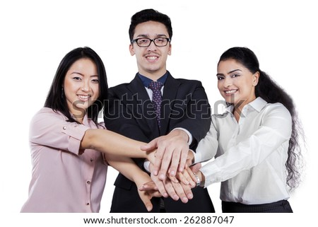 Group of multi ethnic businesspeople joining their hands and smiling at the camera, isolated on white - stock photo