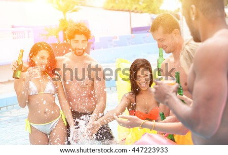 Group of multi ethnic friends having party in pool drinking cocktail and beer - Young people laughing and smiling outdoor in summer time - Vacation and friendship concept - Sunshine color tones filter - stock photo