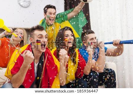 Group of multi-ethnic people celebrating football game - stock photo