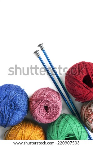 Group of multicolor yarn balls and pair of metallic needles on white as a background - stock photo