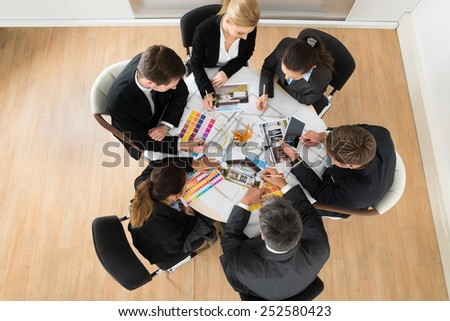 Group Of Multiethnic Businesspeople With Color Samples In Office - stock photo