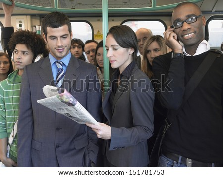 Group of multiethnic commuters in a train with woman reading newspaper - stock photo