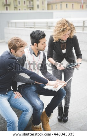 Group of multiethnic contemporary businessman working outdoor with tablet and notebook, discussing - start up, teamwork, business concept - stock photo