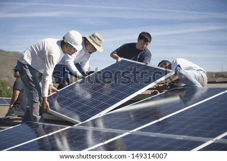 Group of multiethnic engineers placing solar panels on rooftop - stock photo
