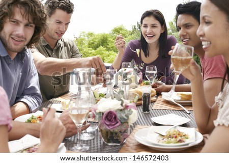 Group of multiethnic friends enjoying dinner party outdoors - stock photo