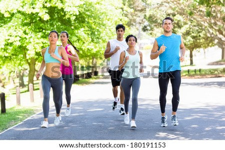 Group of multiethnic marathon athletes running on street - stock photo