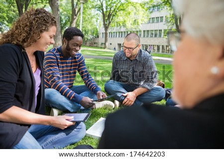 Group of multiethnic university students using digital tablet on campus park - stock photo