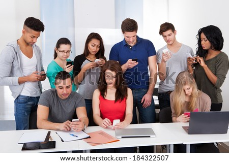 Group of multiethnic university students using mobile phones at desk in classroom - stock photo