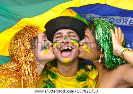 Group of multiethnic young adult fans celebrating victory of the Brazilian soccer team kissing each other - stock photo