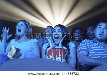 Group of multiethnic young people screaming while watching horror movie in the theatre - stock photo