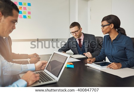 Group of multiracial business colleagues in a meeting seated around a table in the office working on laptops and paperwork - stock photo