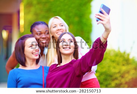 group of multiracial girls taking selfie on smartphone - stock photo